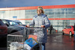 Woman with shopping cart on parking