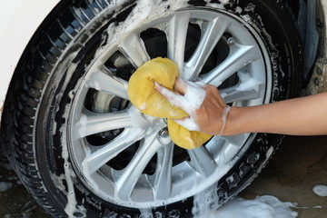 female hand is cleaning car tire with sponge