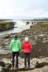 Hikers looking at Iceland nature by waterfall