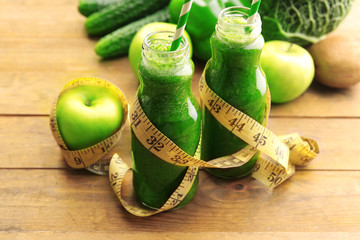 Green fresh healthy juice in glass bottles with fruits and