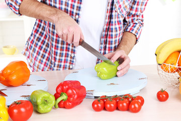 Man cut vegetables in the kitchen
