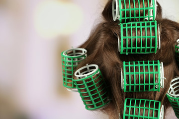Long female hair during hair dressing with curler, close-up,