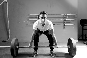 young man on a weightlifting session - crossfit workout.