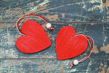 Two red wooden hearts on rustic wooden surface