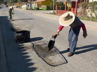 Cantonniers goudronnant une rue à Cuba.