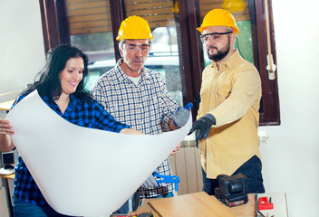 Construction worker and couple looking at the plan