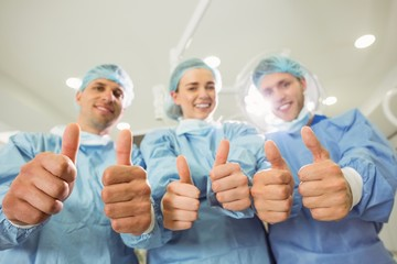 Team of surgeons looking at camera showing thumbs up