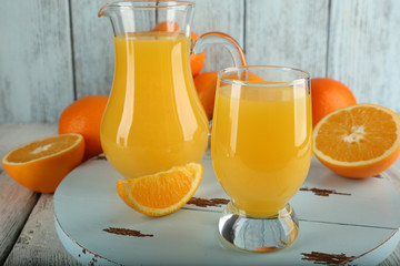 Glass of orange juice with slices on color wooden background