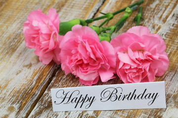 Happy birthday card with pink carnations on rustic wood
