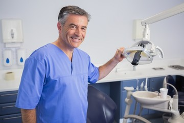 Portrait of a friendly dentist holding light