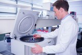 Chemist in lab coat using a centrifuge poster