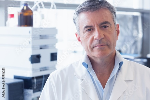 canvas print picture Portrait of an unsmiling scientist wearing lab coat