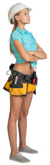 Looking up pretty girl in helmet, shorts, shirt and tool belt