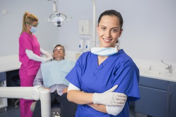 Smiling dentist with arms crossed