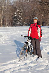 Adult woman having a good time with the bikes in the  snow cover