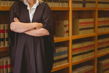 Lawyer leaning on shelf with arms crossed
