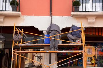 obreros trabajando encima de un andamio
