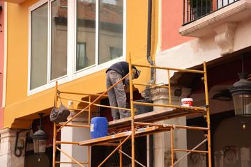 obrero trabajando encima de un andamio