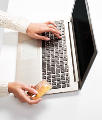 woman's hand enters data using laptop and holding credit card in