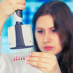 womanl with multi pipette in the laboratory of microbiology