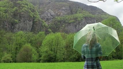 Woman waking in nature with umbrella-Rain