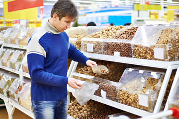 Man buys nuts in a supermarket