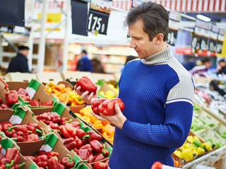 Man chooses bell peppers in store