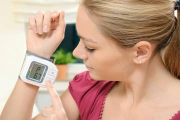 Frau misst Puls und Herzfrequenz mit Messgerät