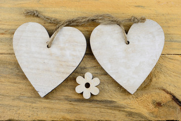 Two wooden hearts with a little baby flower on old wood