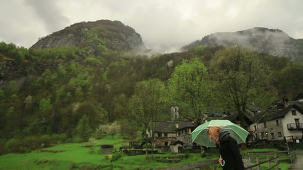 Woman waking under the rain in mountains