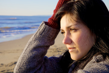 Sad young woman looking sunset on beach in winter