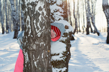 A little girl playing in a birch grove