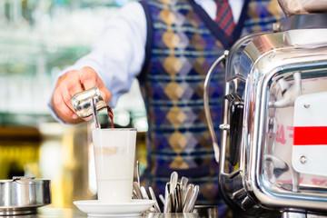 Barista im Cafe gießt Espresso in latte macchiato