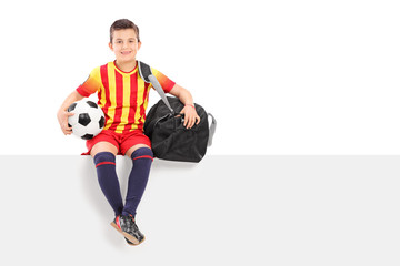 Boy holding a football and sitting on panel