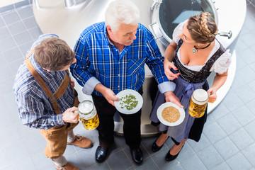 Braumeister und Paar in Bierbrauerei bei Besichtigung