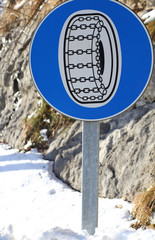 road sign with compulsory snow chains aboard the car