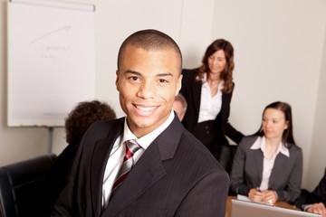 Junger Mann im Meeting mit Kollegen im Hintergrund