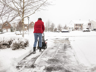 Woman using a snowblower to clear a driveway during snowstorm