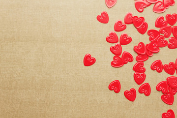 Red hearts confetti on beige background