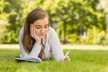 University student lying and writing on notepad
