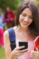 Pretty student sending a text outside on campus