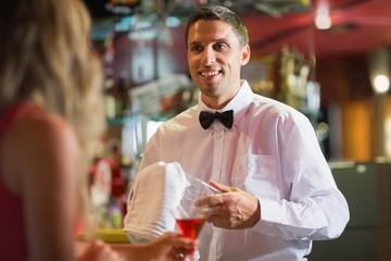 Handsome barman chatting to customer