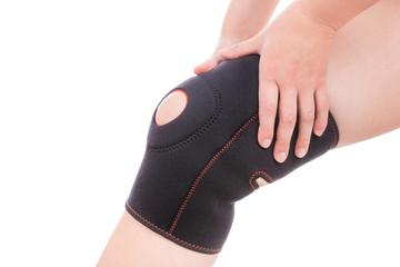 Knee injury. Girl holds hands bandage on his leg.