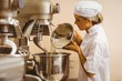 Baker pouring flour into large mixer - 75998481
