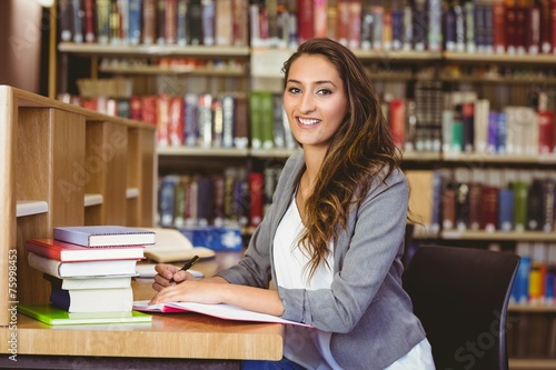 canvas print picture Pretty student writing in her notepad and smiling at camera