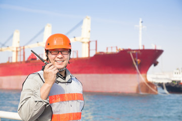 smiling dock worker tholding  radio and  ship background