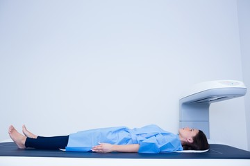 Sick woman lying on a x-ray machine