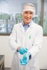 Pharmacist pulling on rubber gloves