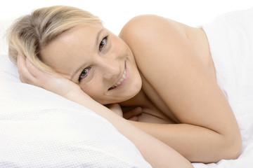 Blonde Frau liegt entspannt im Bett