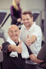 zwei männer im fitness-studio zeigen daumen hoch